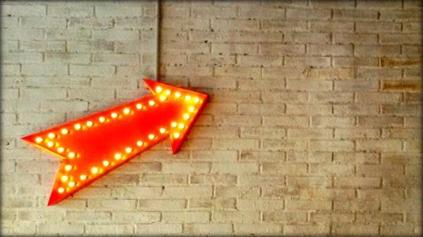 Una pared con una flecha roja que indica hacia dónde ir.